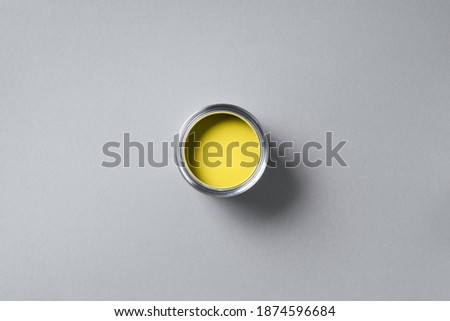 Open paint can on grey background. Appartment renovation, repair, building, design concept. Demonstrating trendy Color of the Year 2021. Illuminating Yellow and Ultimate Gray.