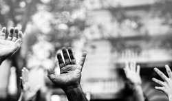 Open palm of a black hand and white hands raised in the air asking for freedom. Multicultural hands in a demonstration on street in black and white. Stop racism. Stop repression.