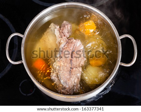 open pan with cooking beef broth with with seasoning vegetables