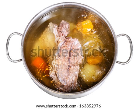 open pan with cooking beef broth with with seasoning vegetables isolated on white background