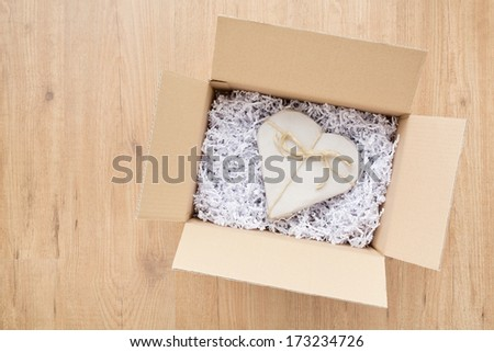 Open parcel box with a heart shaped Valentine\'s Day gift inside it.