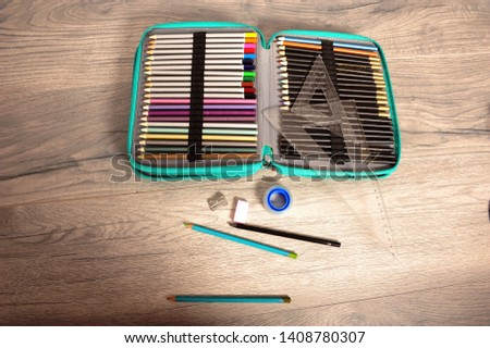 Open pen case with many pencils. Triangle rulers, roll of tape, pencil sharpener and pencils spread out on wooden table. Horizontal image with copy space.
