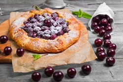 Open pie tart dough sprinkled powdered sugar with ripe cherries on paper on board, fresh cherry in white paper bags, red cherry for pie tart on gray wooden background.