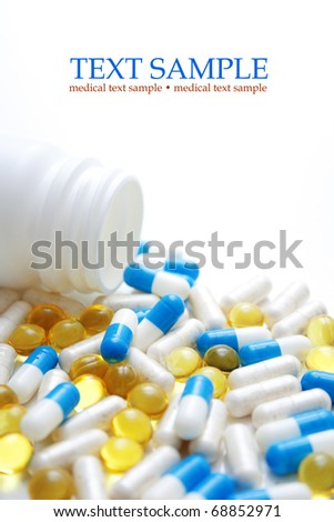 Open pill bottle with medicine spilling out of it isolated on white