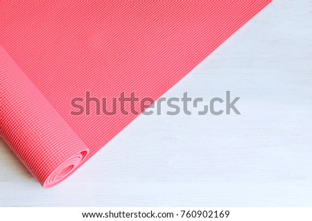 Open pink exercise mat on white wooden background.  Concept for practice yoga, pilates or any  physical workout.