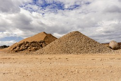 Open pit gravel mining. Large piles of construction sand and gravel used for asphalt production and building. Limestone quarry, mining rocks and stones. Sunny day