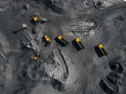 Open pit mine, coal loading in trucks, transportation and logistics, top view aerial.
