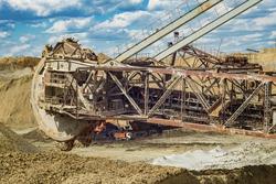 Open pit. Opencast manganese ore mine. Giant excavator machinery. Extractive industry. Big mine, develop mineral resources, excavator digs, metallurgy in Ukraine