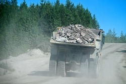 Open-pit operation. Pit dump truck, large-capacity dump truck rides on a gravel wet road works in a granite quarry (gravel pit). Loaded and empty dump trucks, loaded body