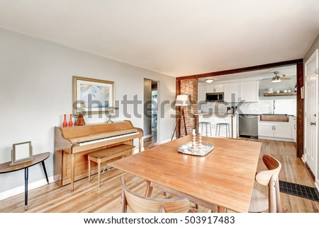 Photo of Open plan dining room interior with piano , wooden table and four chairs. Northwest, USA
