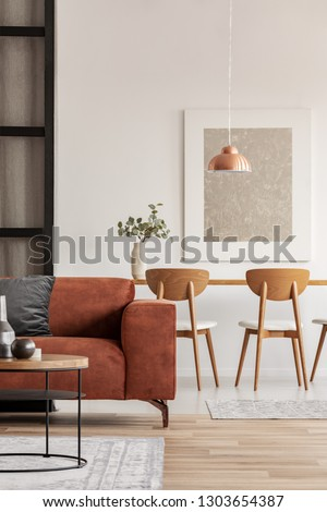 Open plan living and dining room interior with long table with chair and brown velvet settee #1303654387