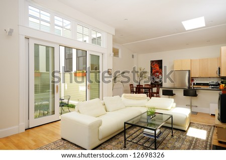 Open plan living room, dining room, kitchen and atrium in modern