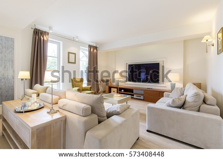 Open plan of a relaxing area with couches, coffee table and TV set #573408448