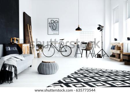 Open plan, white studio flat with sofa, bike, pouf, desk
