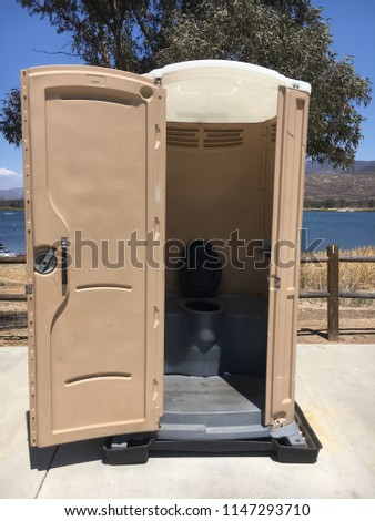 Open portable potty by the lake. #1147293710