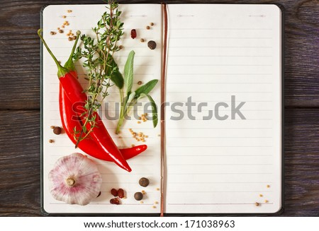 Open Recipe Book With Chili And Spices On A Wooden Background.