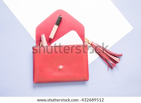 open red clutch bag design with tassel and cosmetics on white and blue background.