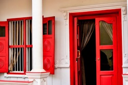 Open Red Door and windows on a colonial house in Fort Kochi (Cochin), Goa, Pondicherry India