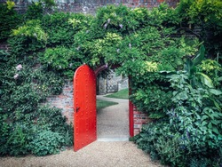 Open, red, half-round door in a brick wall covered with green vines, behind a door a winding gravel path. Lush green foliage cover the brick wall. A mysterious path leads towards the castle walls.