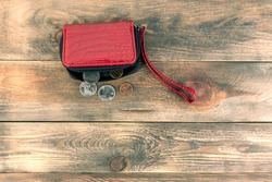 Open red leather pocket wallet with coins one cent and a quarter dollar nearby. Financial crisis, poverty, lack of money. On wooden background. Flat lay. Top view. Copy space for text. Close-up.