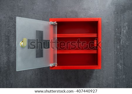 Open red metal empty medicine cabinet hanging on a dark gray marble wall background. Front view #407440927