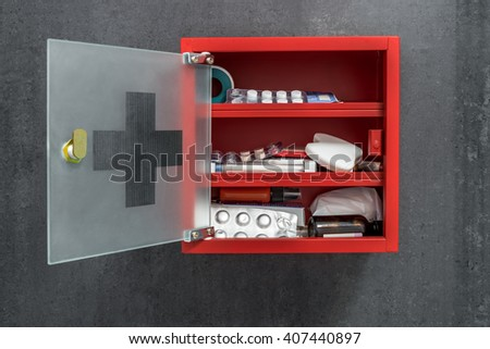 Open red metal medicine cabinet full of drugs hanging on a dark gray marble wall background. Front view #407440897