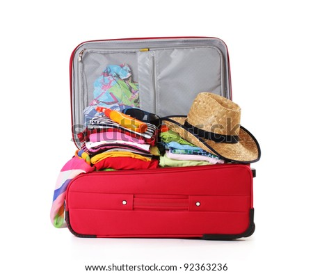 Open red suitcase with clothing isolated on a white