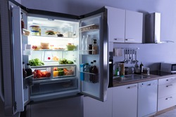 Open Refrigerator Full Of Juice And Fresh Vegetables In Kitchen
