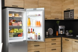 Open refrigerator full of products in kitchen