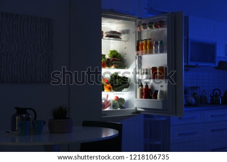 Open refrigerator full of products in stylish kitchen interior at night