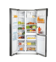 Open refrigerator full of products isolated on white