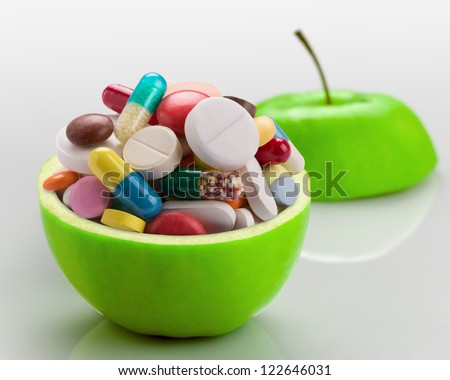 Open ripe apple full of colorful medicines