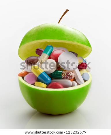 Open ripe apple full of colorful medicines