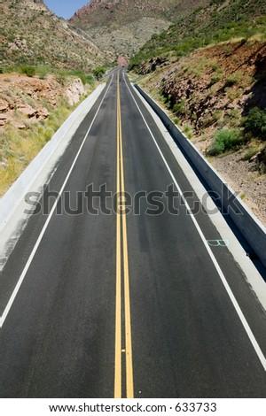 Open road in Arizona desert through mountains