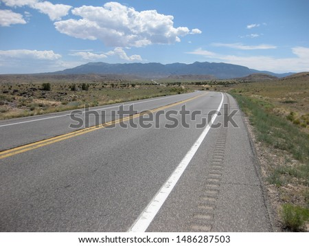 Open road in the high desert of Utah, USA on a bright sunny summer day with few clouds in the sky.  #1486287503