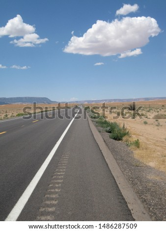 Open road in the high desert of Utah, USA on a bright sunny summer day with few clouds in the sky.  #1486287509