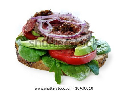 Open roast beef sandwich with avocado, salad, onion, and red onion.  Isolated on white.