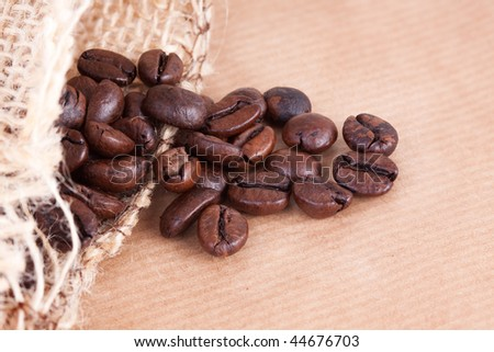 Open sack with some coffee beans fallen from it, against a brown background