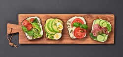Open sandwiches with vegetables, avocado, tomato, mozzarella, boiled egg and soft cheese. Homemade sandwich with ham, cucumber, radish sprouts on wooden board isolated on black, top view, banner