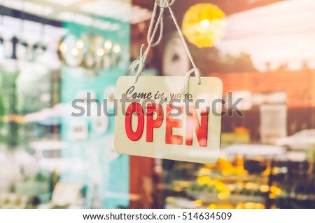 Open sign broad through the glass of door in cafe. Business service and food concept. Vintage tone filter color style.