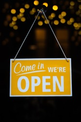 Open Sign on Glass Window With Bokeh Lights in the Background