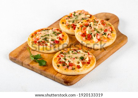 Open small pies, mini pizzas with sausage, pickles, tomatoes, mozzarella, parsley, greens on a wooden board on a white background  ストックフォト ©