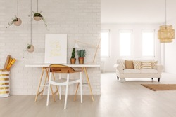 Open space living room interior in real photo with white sofa with cushions in the background, desk with poster and plants standing by the brick wall and plastic chair