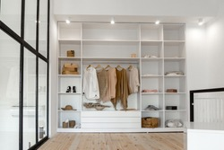 Open space minimalistic scandinavian white wood walk in closet and wardrobe in neutral beige colors