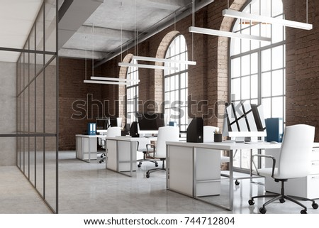 Open space office interior with brick and glass walls, a concrete floor and big windows. A row of computer desks, desktops with blank screens. Side view 3d rendering mock up