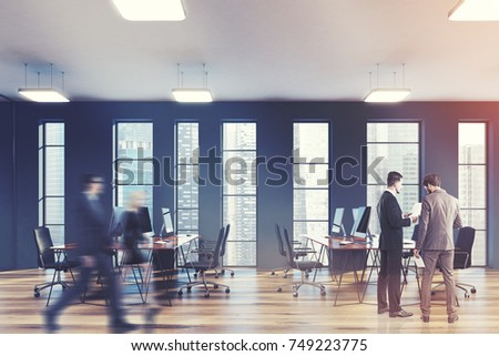 Open space office with gray walls, a wooden floor and narrow windows. Rows of computer desks are standing along them. People. 3d rendering mock up toned image