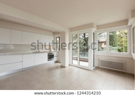 Open space with large windows and modern kitchen. Nobody inside