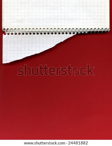 Open spiral notebook and torn paper on red background - stock photo