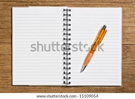 Open spiral notebook with pen on wooden table.