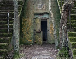 Open steel door of abandoned concrete military bunker in Hel, Poland. World war two and cold war artillery fortification falling apart in the middle of the woods